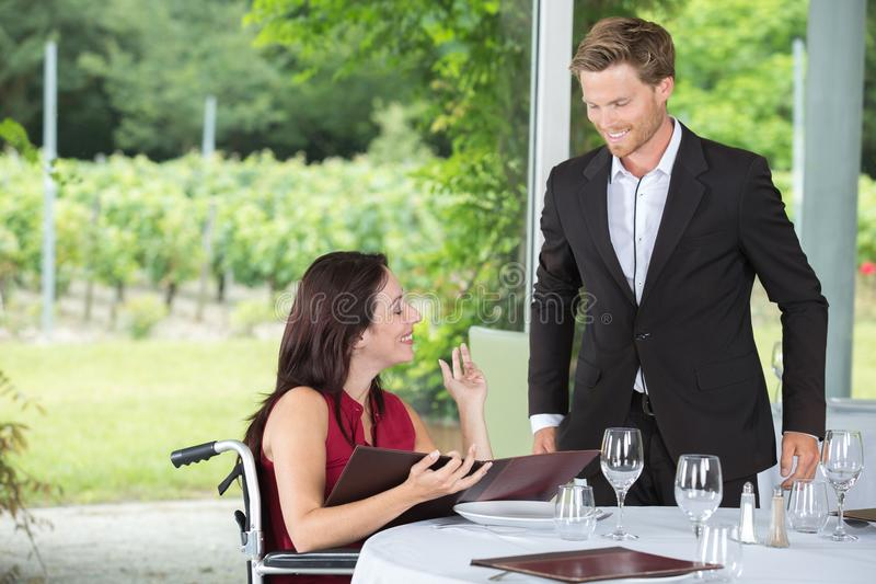 Smiling wheelchair user at restaurant. Smiling wheelchair user at a restaurant royalty free stock images