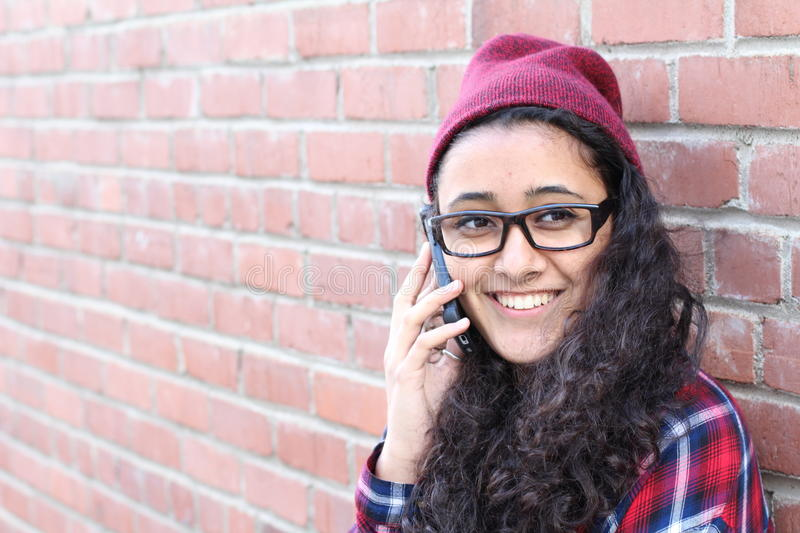 Smiling Winter Hipster Girl in Plaid Shirt and Beanie Hat with Mobile Phone on Brick Wall. Teenage Communication Concept.  royalty free stock photos