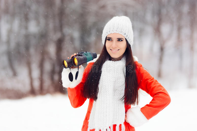 Smiling Winter Woman with Binoculars looking for Christmas. Cute curious girl with scarf and beanie in wintertime stock images