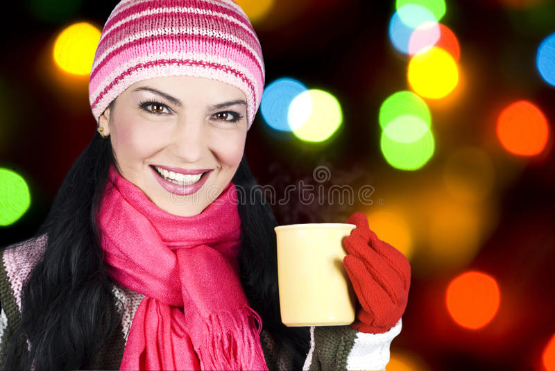 Smiling winter woman holding hot tea. Beautiful happy smiling woman dressed with winter clothes holding a hot tea mug with steam and having Christmas lights in