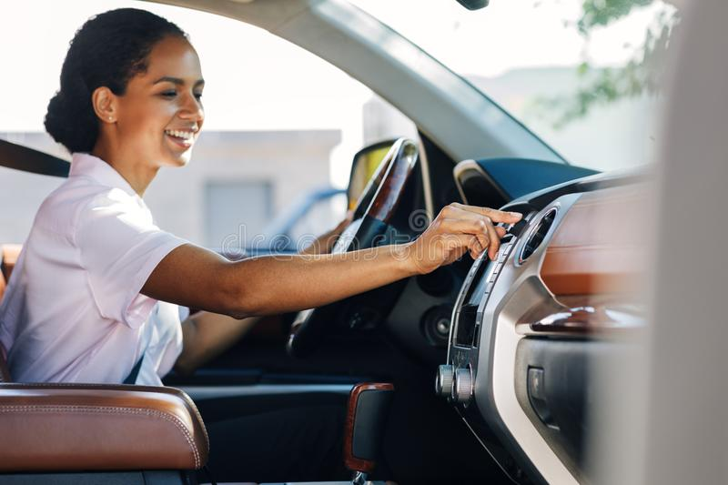 Smiling woman adjusting knob on dashboard stock photos