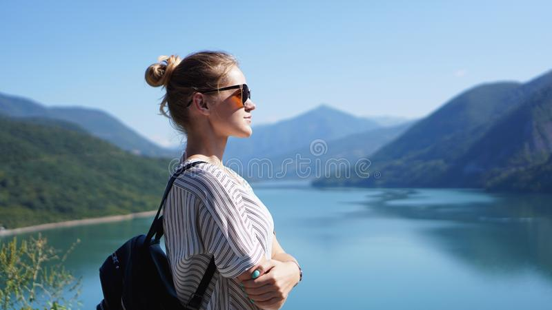 Smiling woman against mountain landscape and lake royalty free stock photos