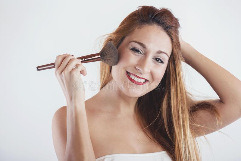 Smiling woman applying make up with a big brush. On white background stock photography