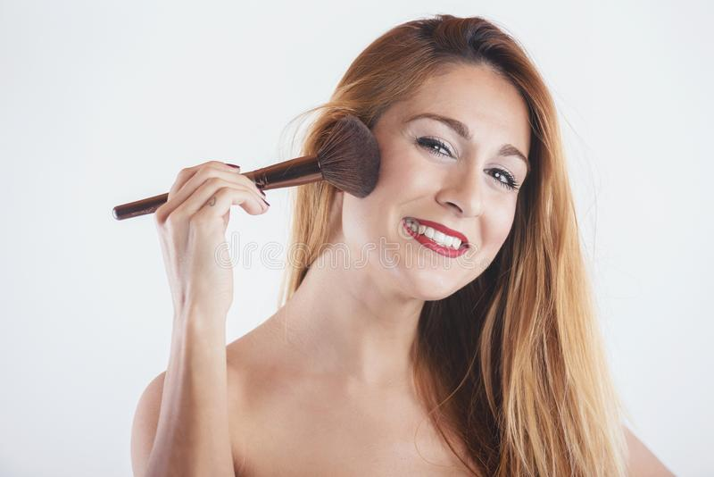 Smiling woman applying make up with a big brush. On white background stock images