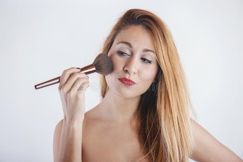 Smiling woman applying make up with a big brush. On white background royalty free stock images