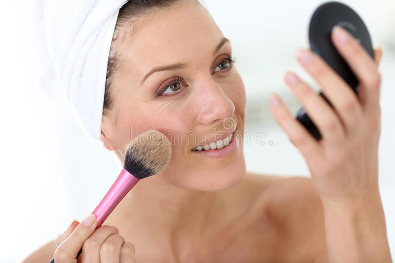 Smiling woman applying powder on her face royalty free stock photography