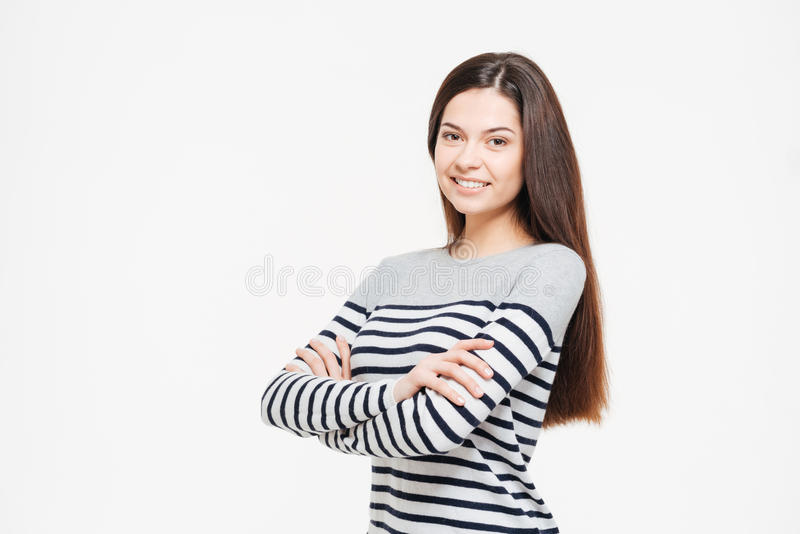 Smiling woman with arms folded looking at camera. Isolated on a white background stock photo