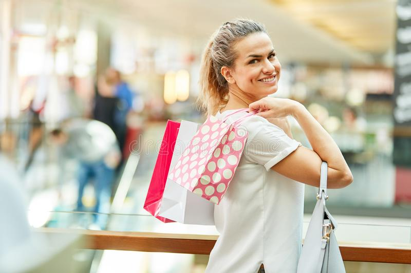 Smiling woman as a customer in retail. With shopping bags while shopping royalty free stock image