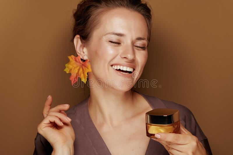 Smiling woman with autumn leaf earring holding facial creme royalty free stock images