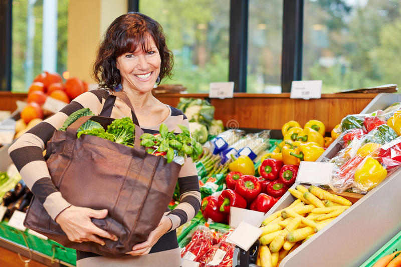 Smiling woman with bag full of vegetables royalty free stock image