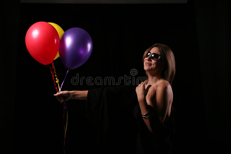 Smiling woman with ballons. Smiling happy woman expression with helium ballons in dark royalty free stock images