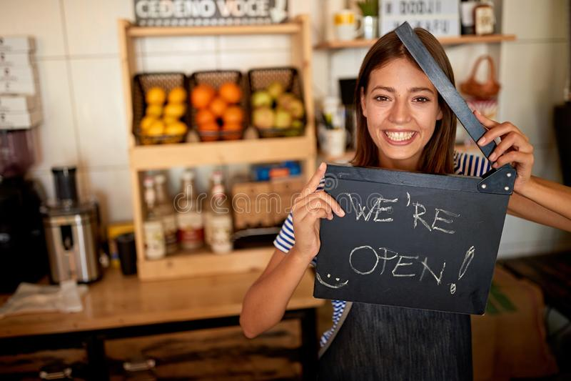 Woman barista holding Open Sign. woman opening her store royalty free stock photos