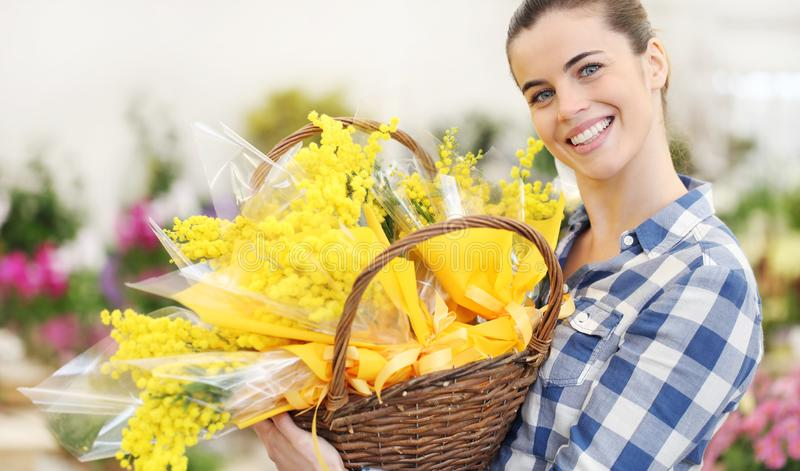 Smiling woman with basket of mimosa spring flowers, 8 March Women`s Day concept royalty free stock images