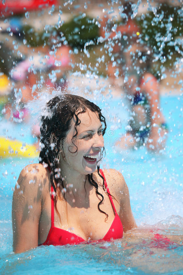 Smiling woman bathes in pool under splashes