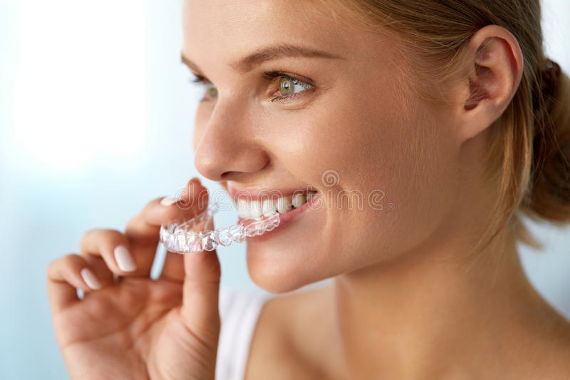 Smiling Woman With Beautiful Smile Using Invisible Teeth Trainer royalty free stock image