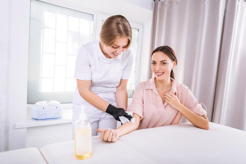 Woman smiling while communicating with her depilatory master. Smiling woman. Beautiful women smiling while communicating with her favorite depilatory master stock photo