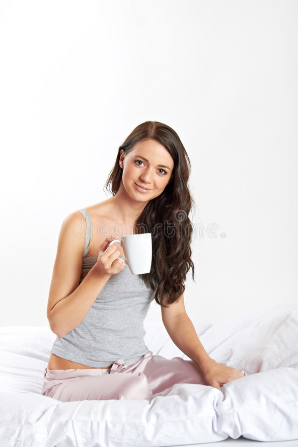 Smiling woman in bed with coffee