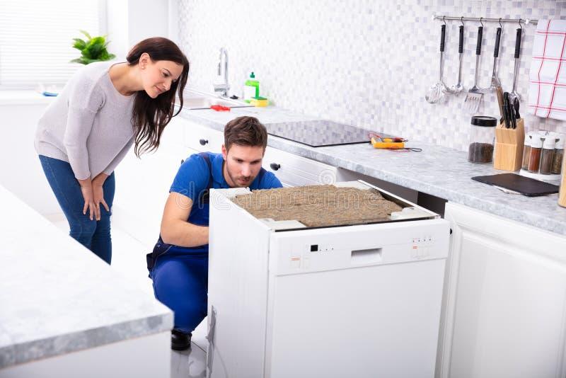 Serviceman Repairing Dishwasher In Kitchen royalty free stock image