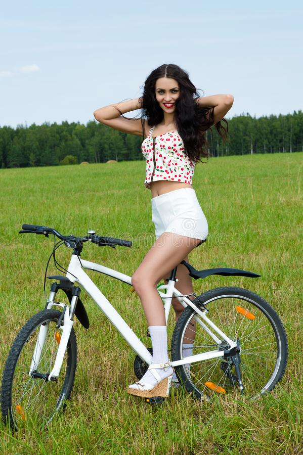 Smiling woman on bicycle in the field royalty free stock photography