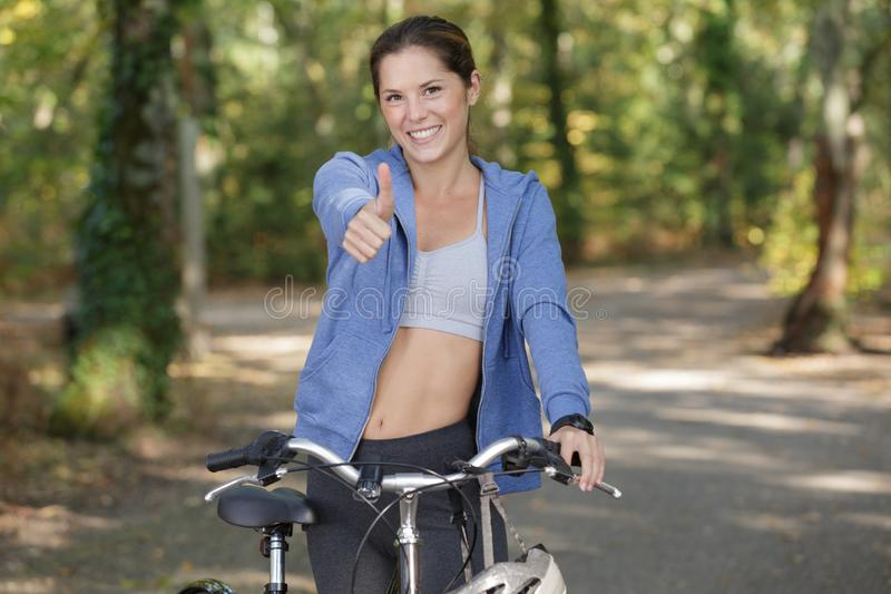 Smiling woman with bicycle gesturing thumb up stock photos