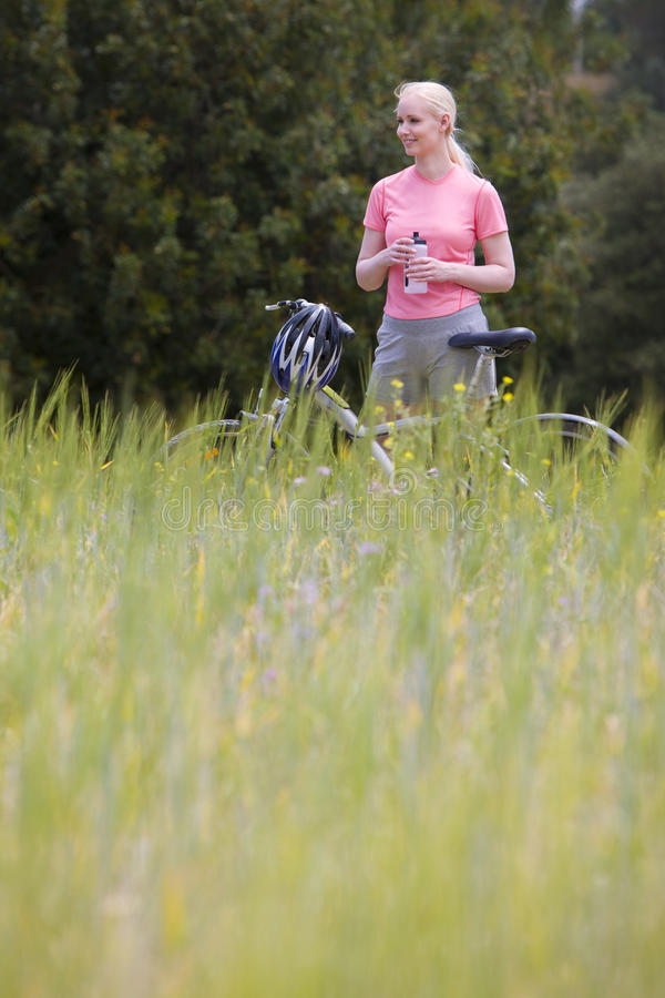 Smiling woman with bicycle holding water bottle in rural field royalty free stock photo
