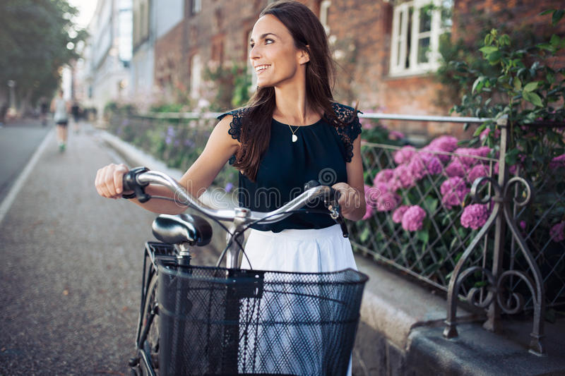 Smiling woman with bike walking down the street royalty free stock photo