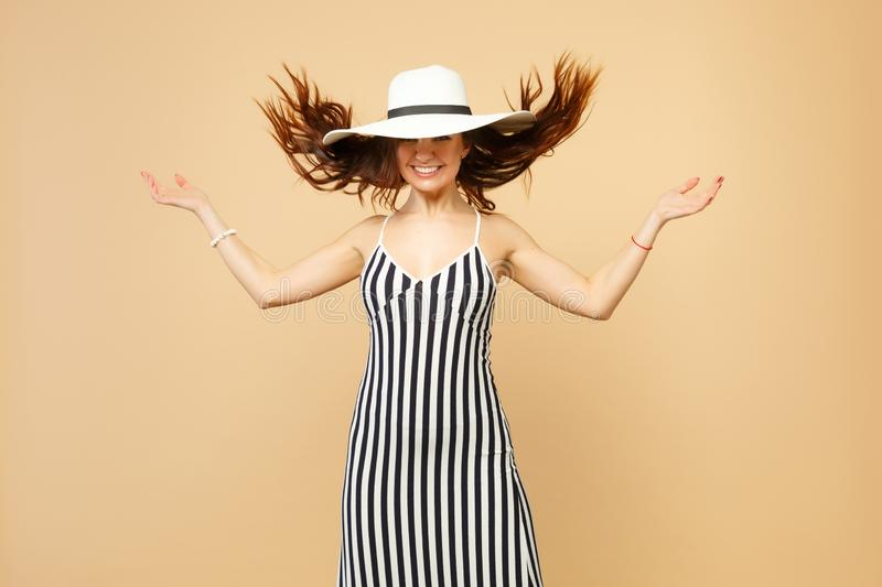 Smiling woman in black and white striped dress, hat with flying hair spreading hands isolated on pastel beige wall stock image