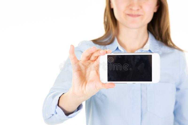 Smiling woman in blue shirt showing blank black smartphone screen royalty free stock images