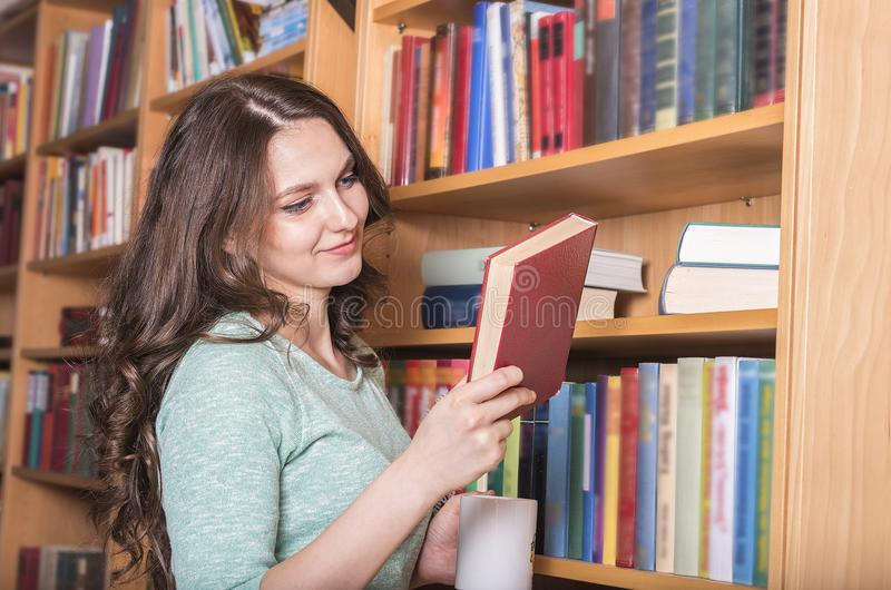 Smiling woman with a book in hand royalty free stock photo