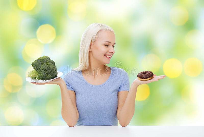 Smiling woman with broccoli and donut royalty free stock photography
