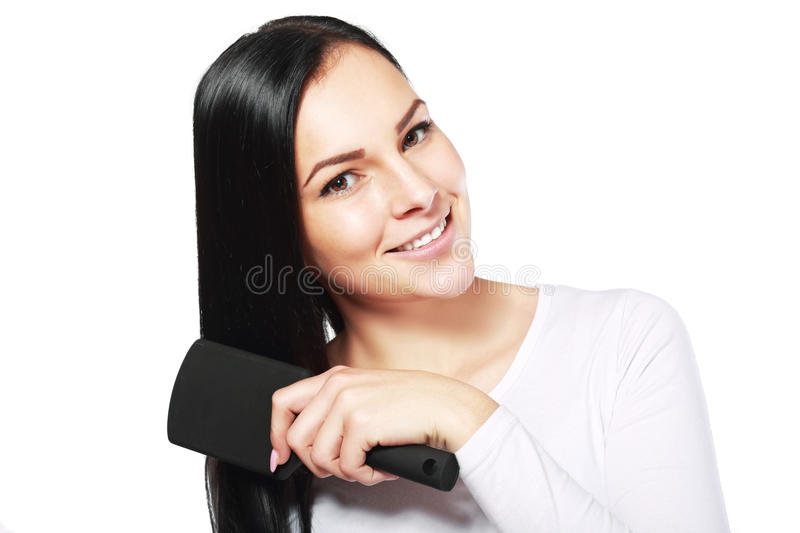 Smiling woman brushing her hair. Attractive smiling woman brushing her hair t on white background royalty free stock image