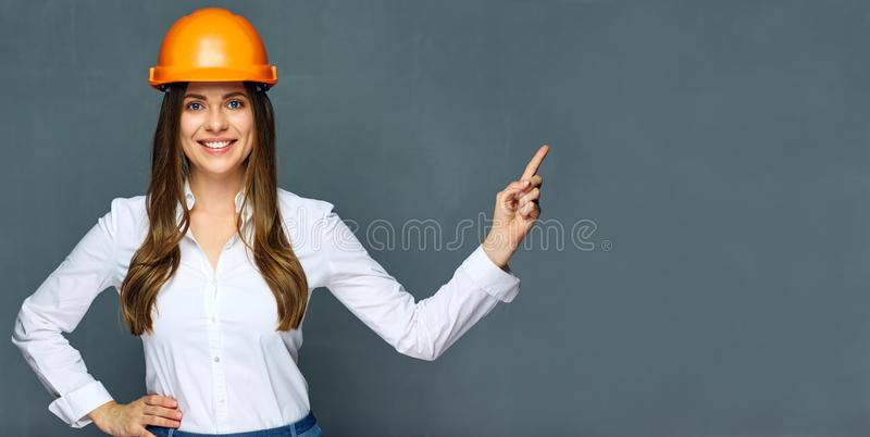 Smiling woman builder engineer pointing finger at copy space. royalty free stock photography