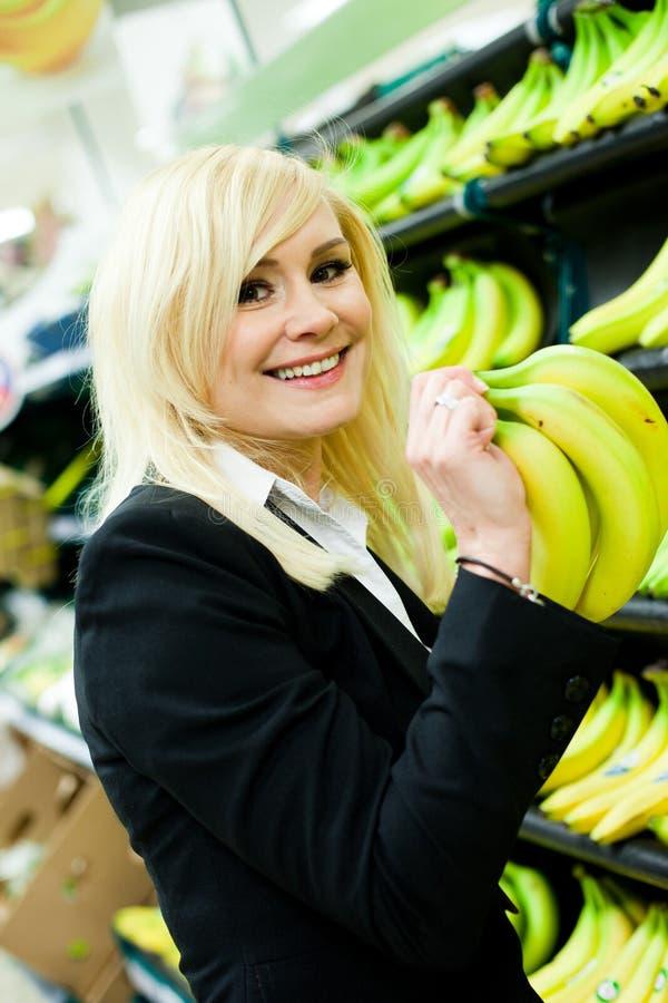 Download Smiling Woman Buying Bananas Stock Photo - Image of potassium, counter: 24544444