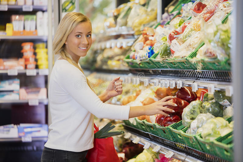 Smiling Woman Buying Capsicum In Supermarket royalty free stock photo