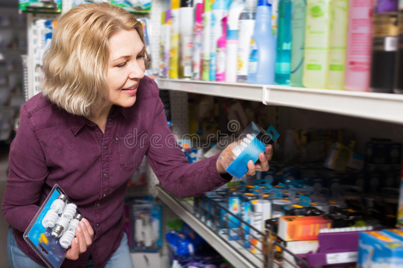 Smiling woman buys light bulbs at the store royalty free stock photo