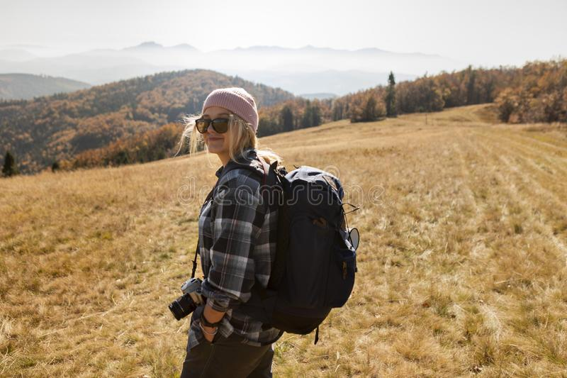 Smiling woman in a cap with backpack hiking the mountains. Smiling woman in a cap and sunglasses with backpack hiking the mountains. Model is wearing a pink cap stock photography
