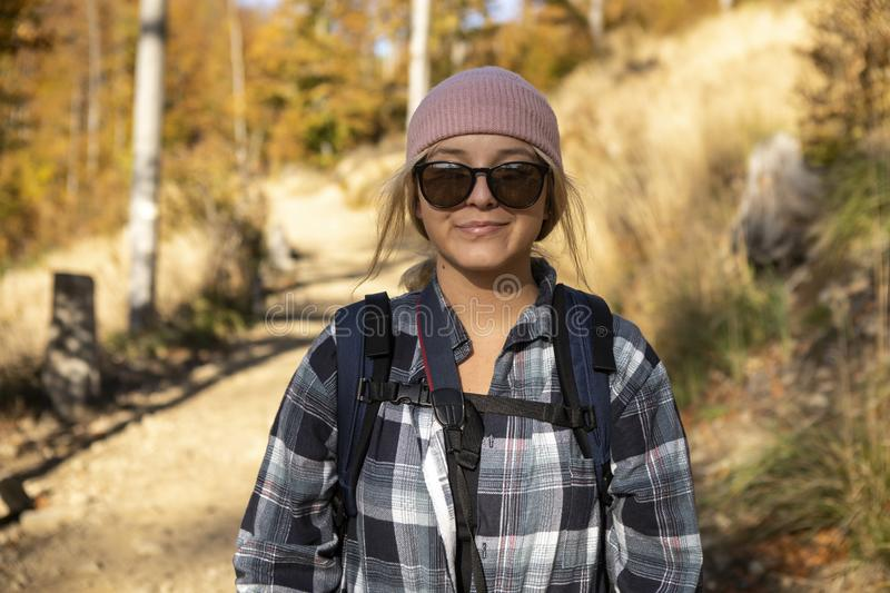 Smiling woman in a cap with backpack hiking the mountains. Smiling woman in a cap and sunglasses with backpack hiking the mountains. A beautiful morning in the stock photos