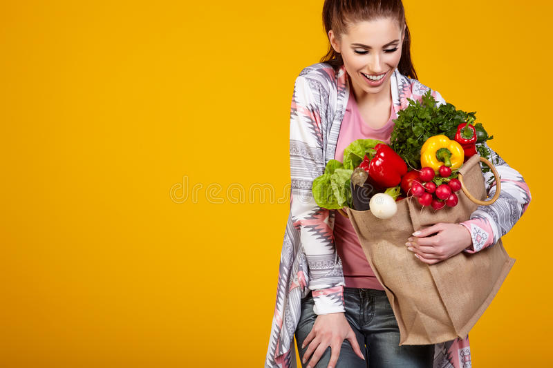 Smiling woman carrying a bag with vegetables. Yellow background royalty free stock photography