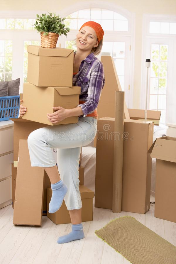 Smiling woman carrying boxes royalty free stock photography
