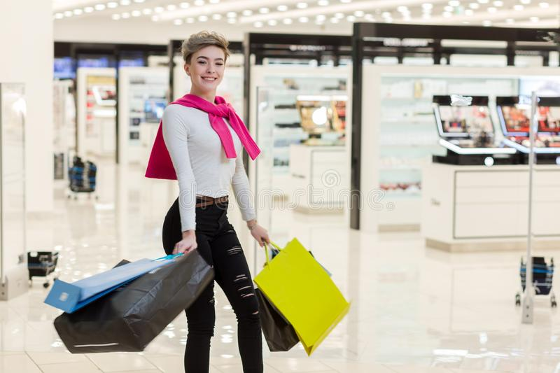 Smiling woman carrying some shopping bags with shops on the background royalty free stock images