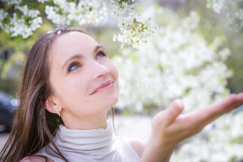 Smiling woman catching white petals stock photography