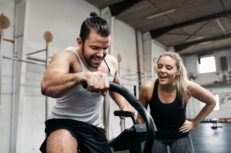 Smiling woman cheering on her gym partner riding a bike stock image