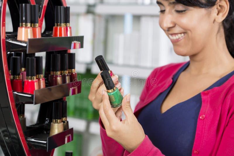 Smiling Woman Choosing Nail Polish In Pharmacy stock photo