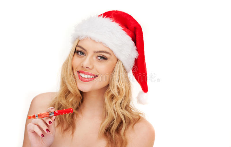 Smiling woman with Christmas e-cigarette. Smiling beautiful blond woman with a festive red Christmas e-cigarette vaporizer in her hand posing with bare shoulders stock photo