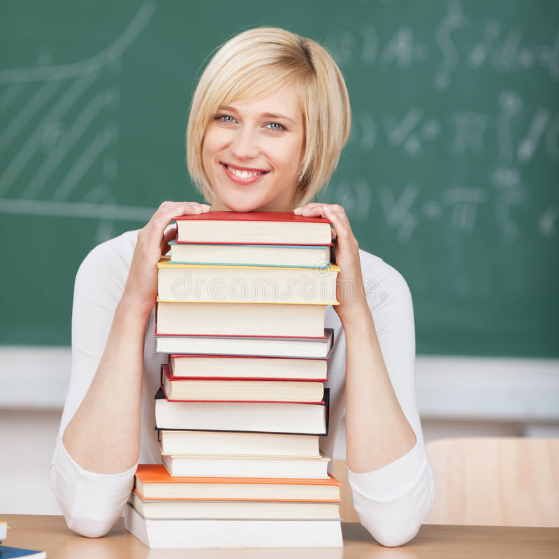 Smiling woman in classroom on stacked books royalty free stock image