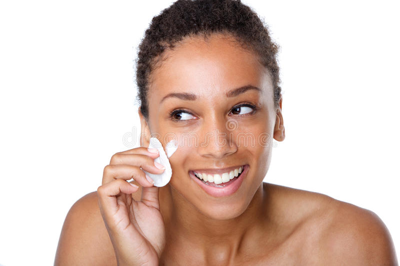 Smiling woman cleaning face with make up sponge stock image