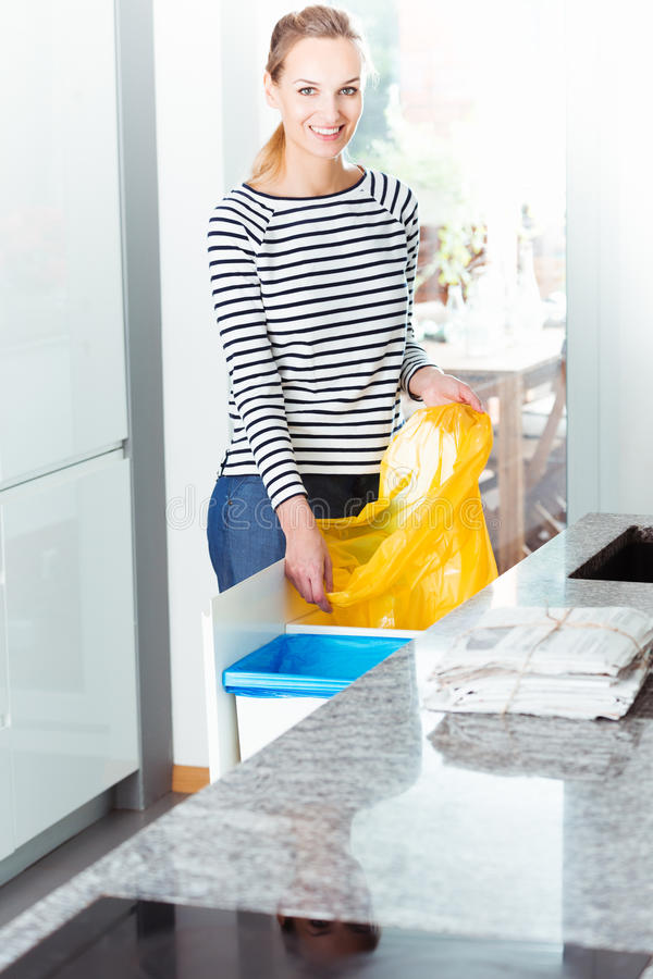 Woman changing bag for recycling. Smiling woman cleaning modern kitchen and changing bin bag for recycling waste stock photo
