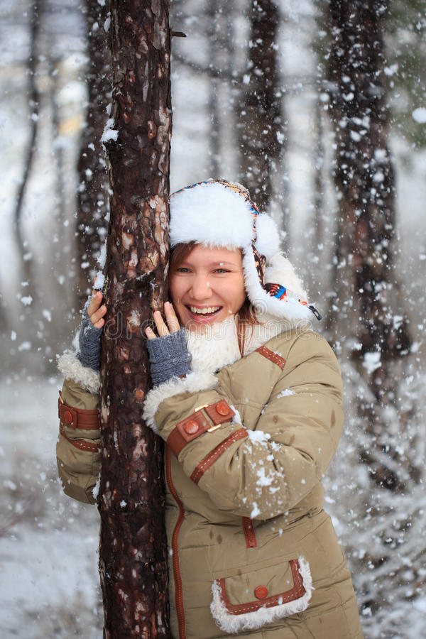 Smiling woman in coat with white fur, hat with ear flaps and grey fingerless knitted mittens hugs a tree in winter forest with fa. Young beautiful smiling woman royalty free stock photography