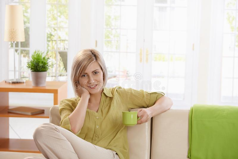 Smiling woman with coffee. Smiling woman sitting on sofa in bright living room, holding coffee mug, looking at camera royalty free stock images