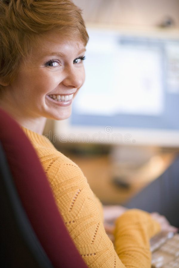 Smiling woman at computer. A smiling young woman working at the computer stock photography